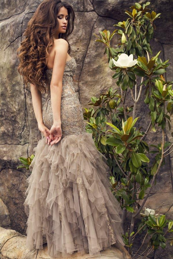 Mooie vrouw met lang krullend haar in luxueuze kleding stock afbeelding
