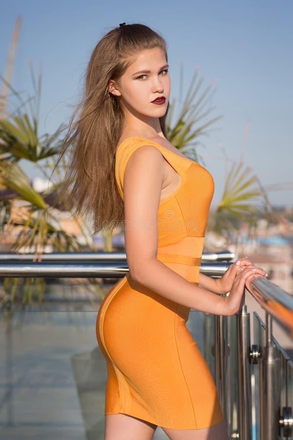 Mooie vrouw met lang lichtbruin haar in een korte oranje kleding op het achtergrondrijkdomhotel royalty-vrije stock afbeelding