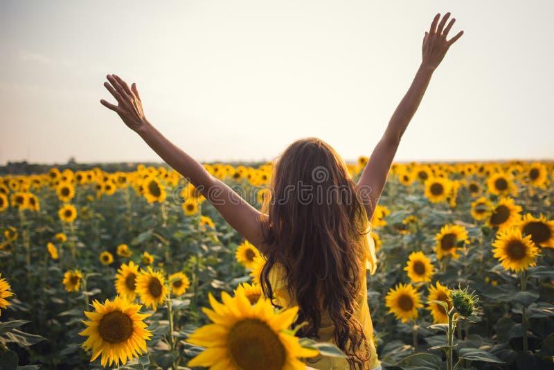 Mooie vrouw met lange haarhanden omhoog op een gebied van zonnebloemen royalty-vrije stock foto
