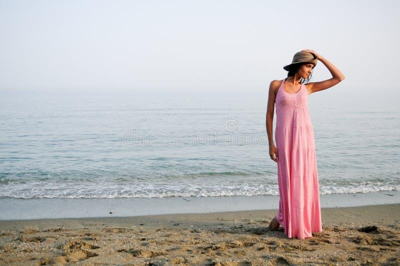 Mooie vrouw met lange roze kleding op een tropisch strand royalty-vrije stock fotografie
