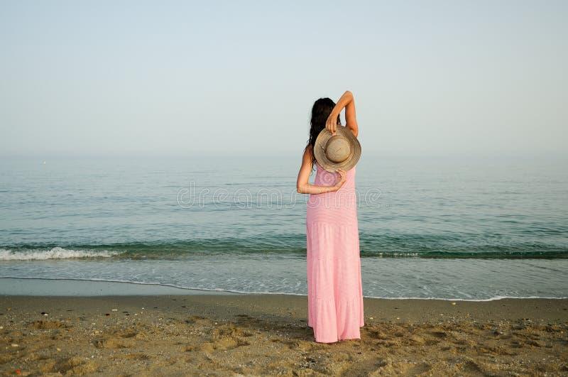 Mooie vrouw met lange roze kleding op een tropisch strand stock afbeelding