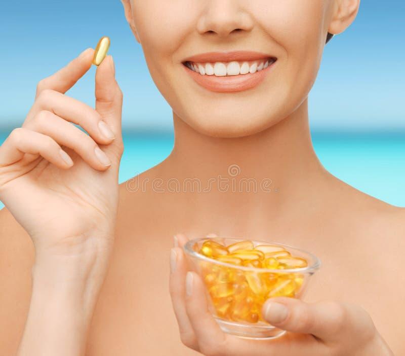 Mooie vrouw met omega 3 vitaminen stock foto's