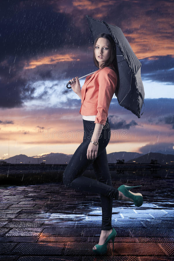 Mooie vrouw met paraplu, die in profiel wordt gedraaid stock foto's