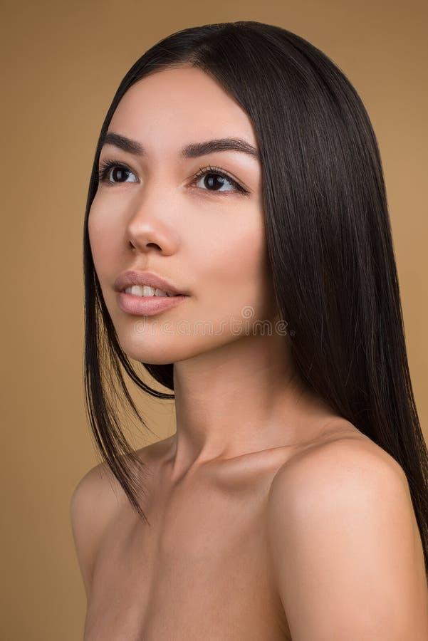 Mooie Vrouw met Perfect die de Studioportret van de Huidschoonheid op Beige Achtergrond wordt geïsoleerd stock foto