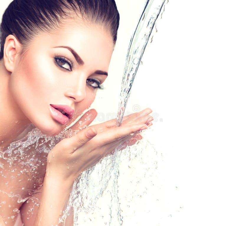 Mooie vrouw met plonsen van water in haar handen stock foto