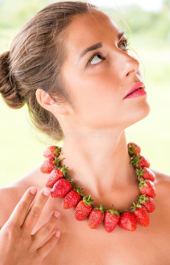 Mooie vrouw met rode die parels van verse aardbei worden gemaakt royalty-vrije stock afbeelding