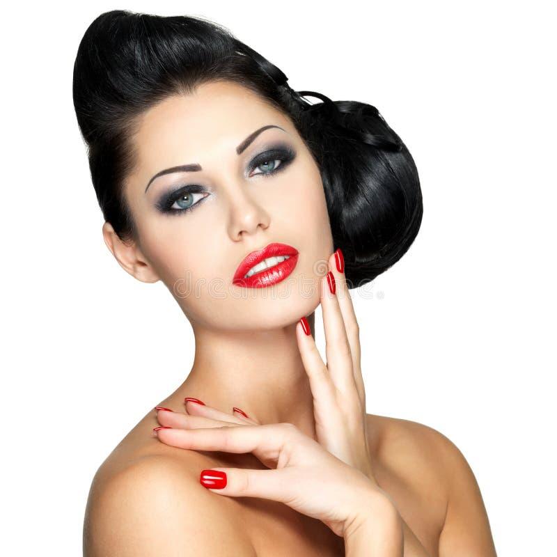 Mooie vrouw met rode spijkers en maniermake-up royalty-vrije stock afbeelding