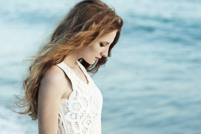 Mooie vrouw met rood haar bij het overzees stock foto