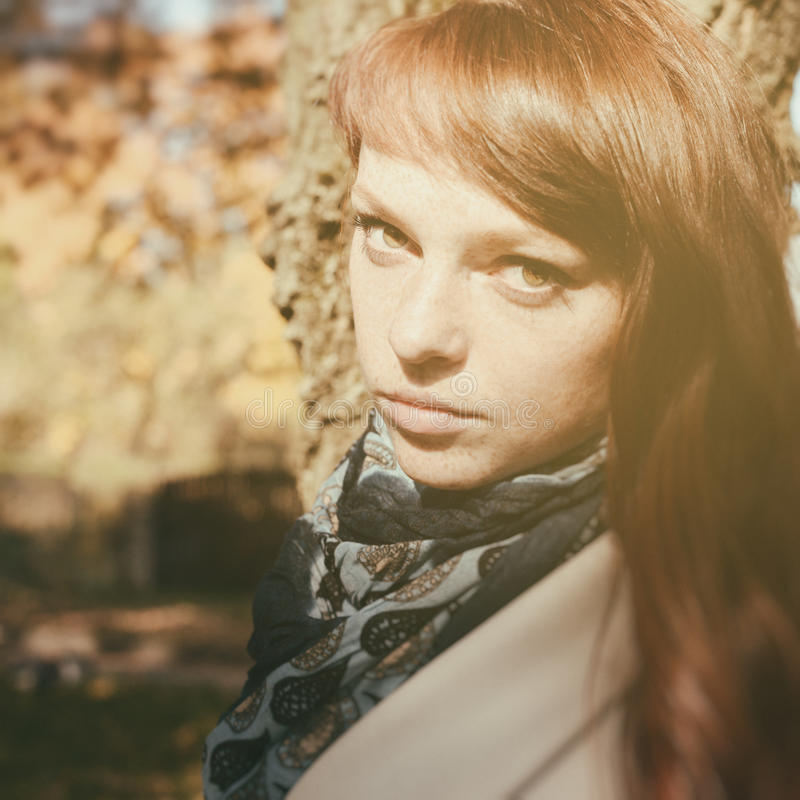 Mooie vrouw met rood haar in de herfstpark royalty-vrije stock foto