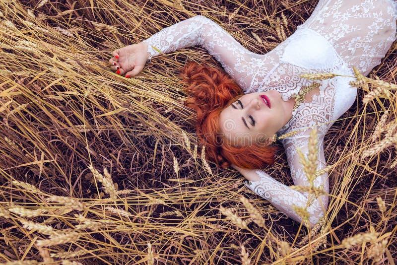 Mooie vrouw met rood haar die in een tarwegebied liggen stock afbeelding