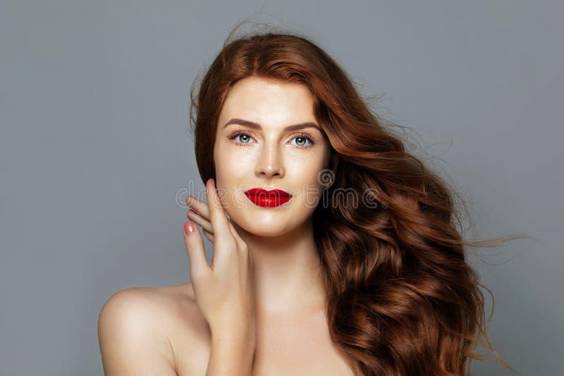 Mooie vrouw met rood krullend haar Vrolijk roodharigemodel op blauw portret als achtergrond royalty-vrije stock afbeelding