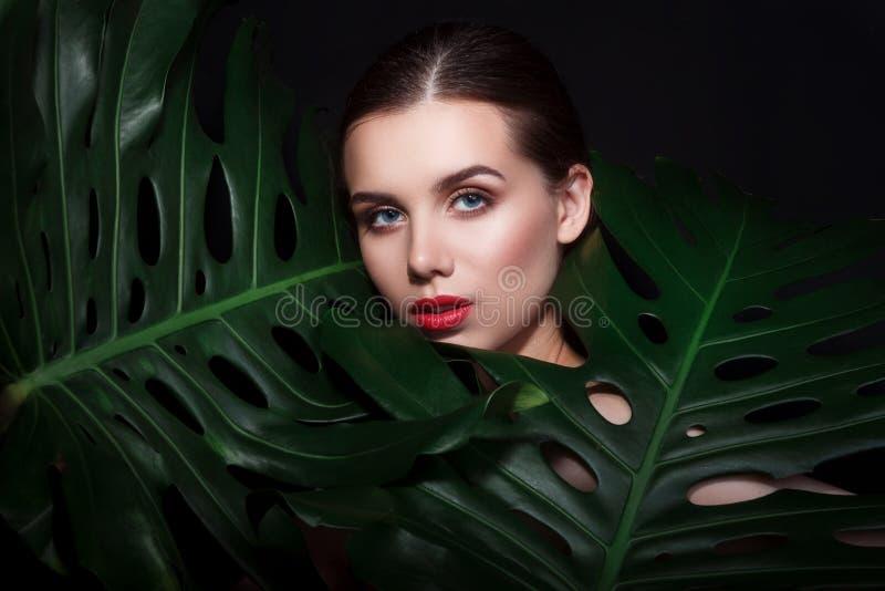 Mooie vrouw met samenstelling en rode lippen in groene bladeren stock foto's