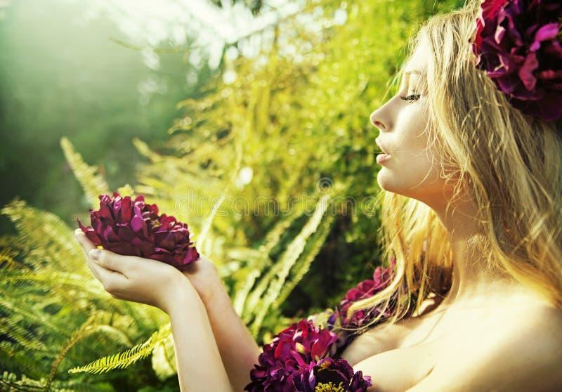 Mooie vrouw met schitterende bloem stock fotografie