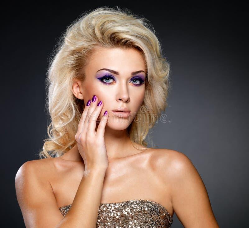 Mooie vrouw met schoonheids purpere manicure en make-up van ogen. stock fotografie