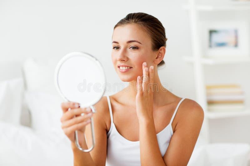 Mooie vrouw met spiegel wat betreft haar gezichtshuid royalty-vrije stock foto's