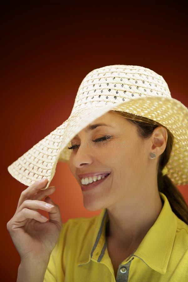 Mooie vrouw met strohoed die en pret glimlachen hebben stock foto's