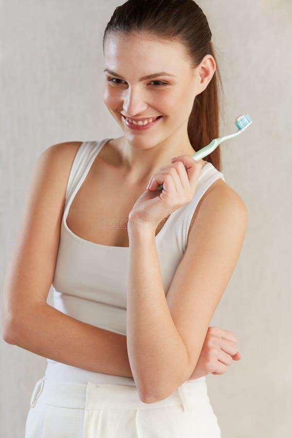 Mooie vrouw met tandenborstel Tandzorgachtergrond royalty-vrije stock foto