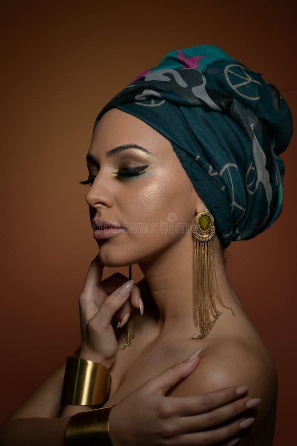 Mooie vrouw met tulband Jong aantrekkelijk wijfje met tulband en gouden toebehoren Schoonheids modieuze vrouw stock afbeeldingen