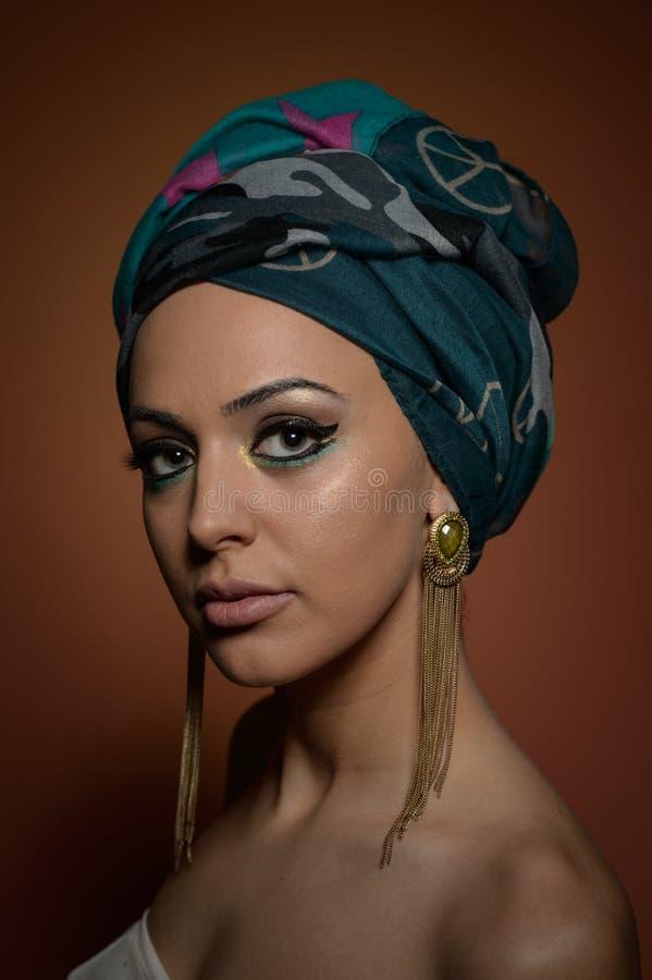Mooie vrouw met tulband Jong aantrekkelijk wijfje met tulband en gouden toebehoren Schoonheids modieuze vrouw stock fotografie