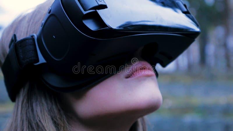 Mooie vrouw met virtuele werkelijkheid in openluchtpark VR het apparaat van hoofdtelefoonglazen Jonge vrouw in een VR-glazen in h stock afbeeldingen