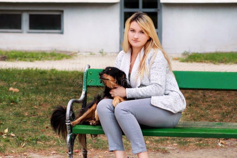 Mooie vrouw met zijn kleine gemengde rassenhond zitting en het stellen voor camera op houten bank bij stadspark royalty-vrije stock afbeelding