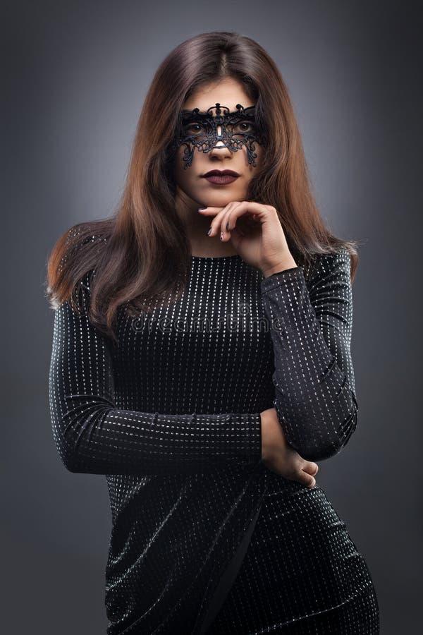 Mooie vrouw met zwart kantmasker over haar ogen op de donkergrijze achtergrond royalty-vrije stock foto's