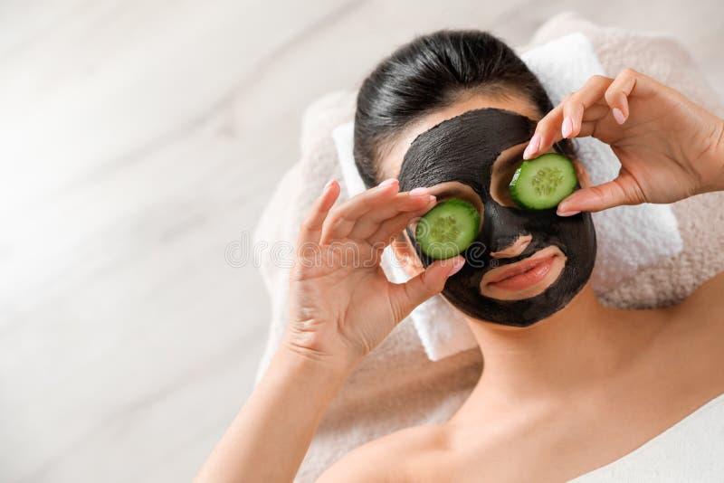 Mooie vrouw met zwart masker die op gezicht en komkommerplakken in kuuroordsalon ontspannen, hoogste mening royalty-vrije stock afbeelding