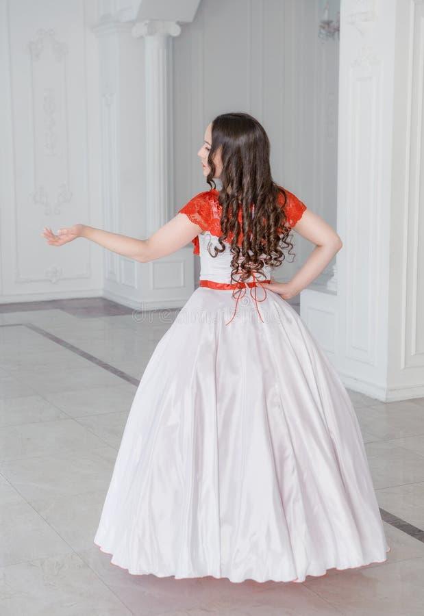 Mooie vrouw in middeleeuwse kleding met hoepelrok De rug stelt stock foto's