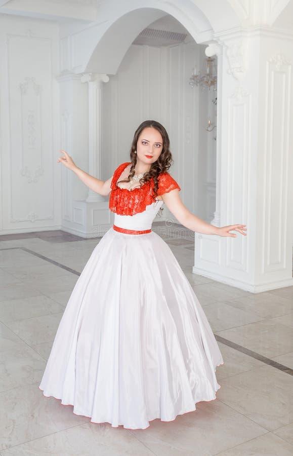Mooie vrouw in middeleeuwse kleding met hoepelrok in de zaal stock fotografie