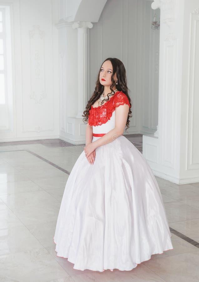 Mooie vrouw in middeleeuwse kleding met hoepelrok in de zaal royalty-vrije stock afbeeldingen