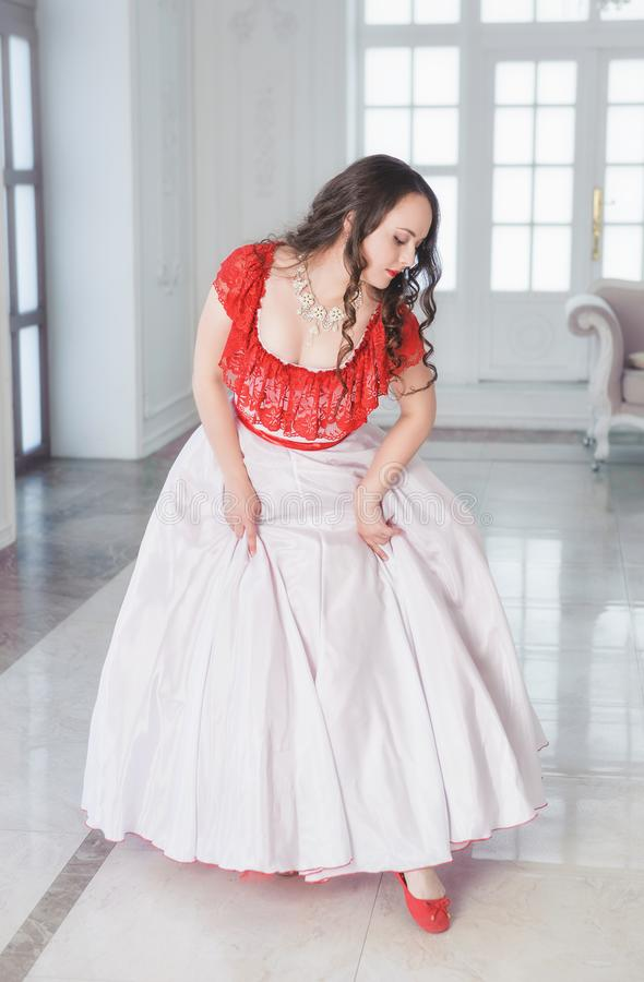 Mooie vrouw in middeleeuwse kleding met hoepelrok in de zaal royalty-vrije stock foto