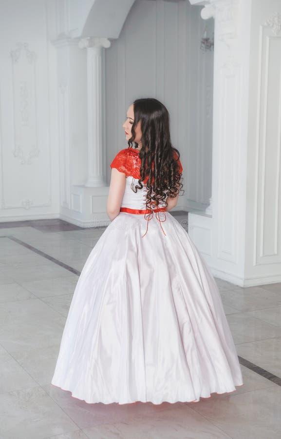 Mooie vrouw in middeleeuwse kleding met hoepelrok in de zaal bedelaars stock foto