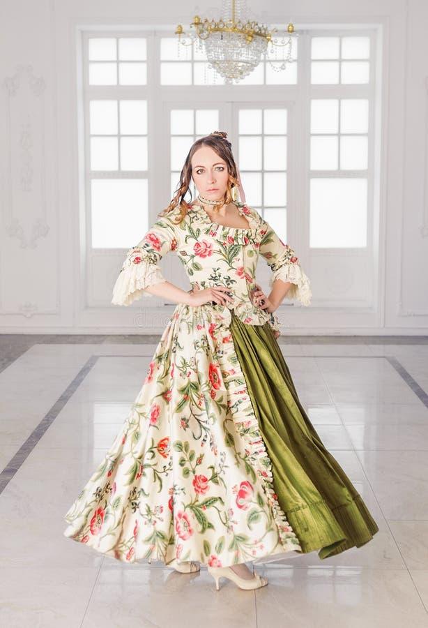 Mooie vrouw in middeleeuwse kleding met hoepelrok het dansen stock afbeelding