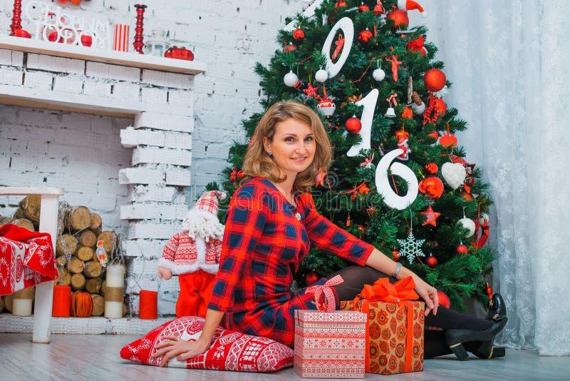 Mooie vrouw netto aan Kerstmisboom, rode kleding royalty-vrije stock afbeelding