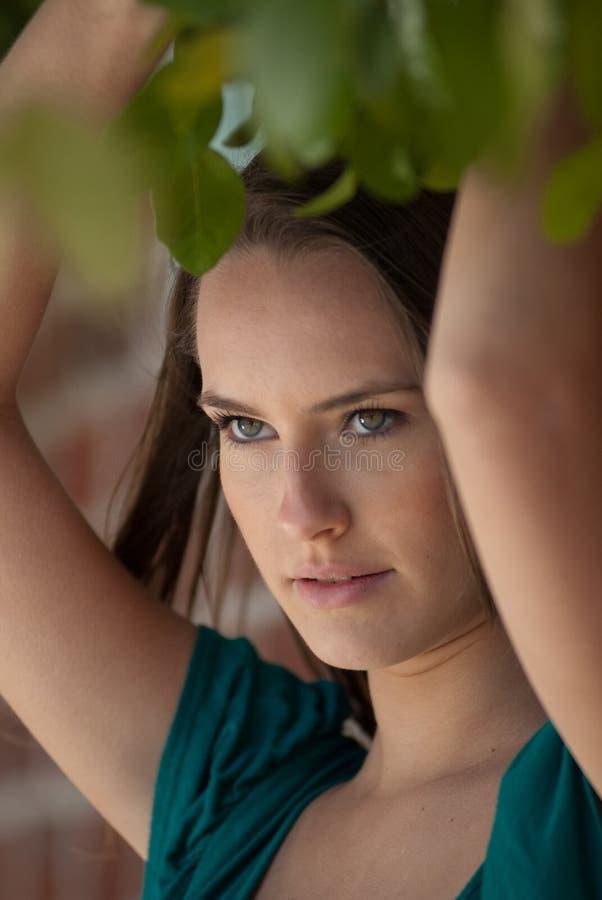 Mooie vrouw onder bladeren royalty-vrije stock afbeelding