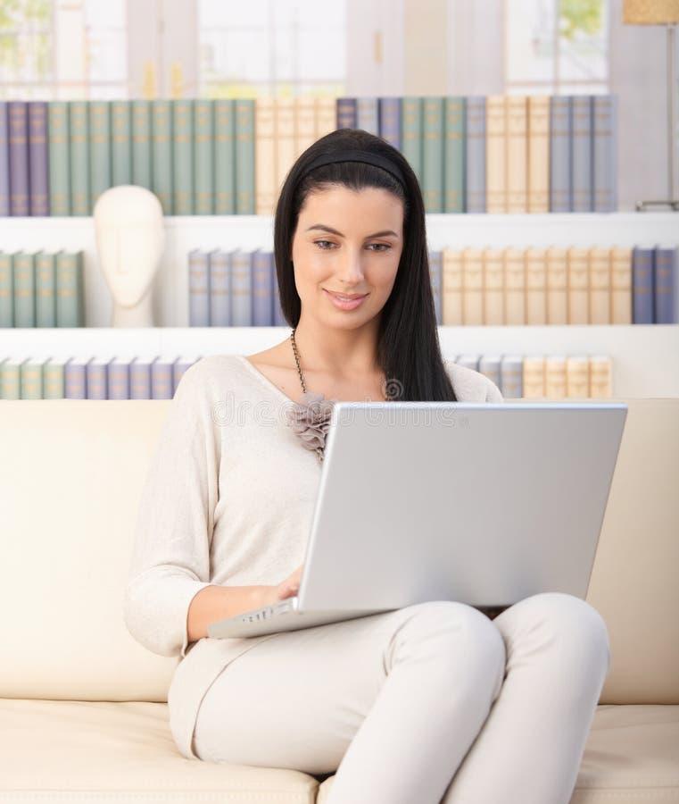 Mooie vrouw op bank met laptop royalty-vrije stock foto