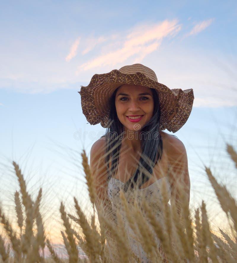 Mooie vrouw op een gouden graangewassengebied in de zomer royalty-vrije stock foto