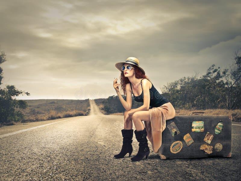 Mooie vrouw op een koffer stock afbeelding