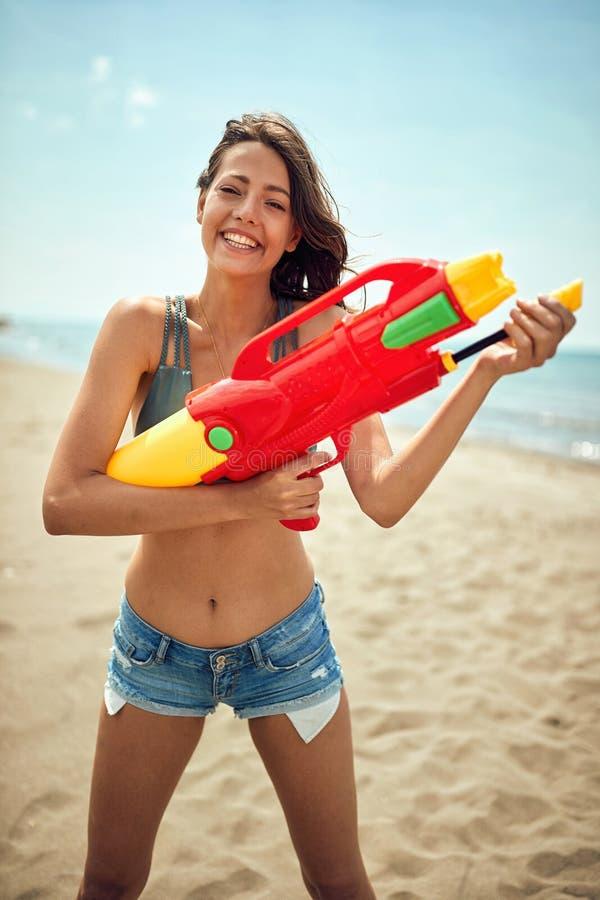 Mooie vrouw op een strand met stuk speelgoed waterkanon stock foto's