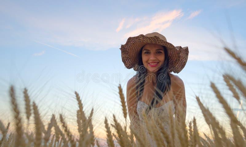 Mooie vrouw op gouden graangewassengebied in de zomer royalty-vrije stock fotografie