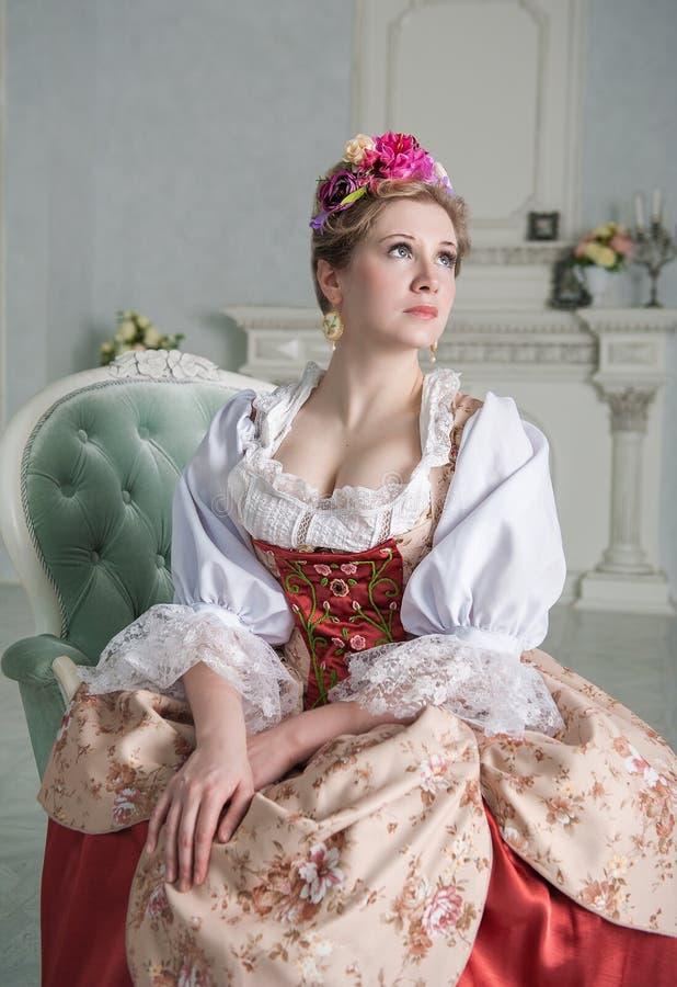Mooie vrouw in ouderwetse middeleeuwse kleding op de bank stock foto's