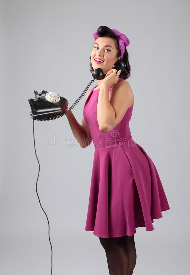 Mooie vrouw in purpere kleding met uitstekende zwarte telefoon royalty-vrije stock foto
