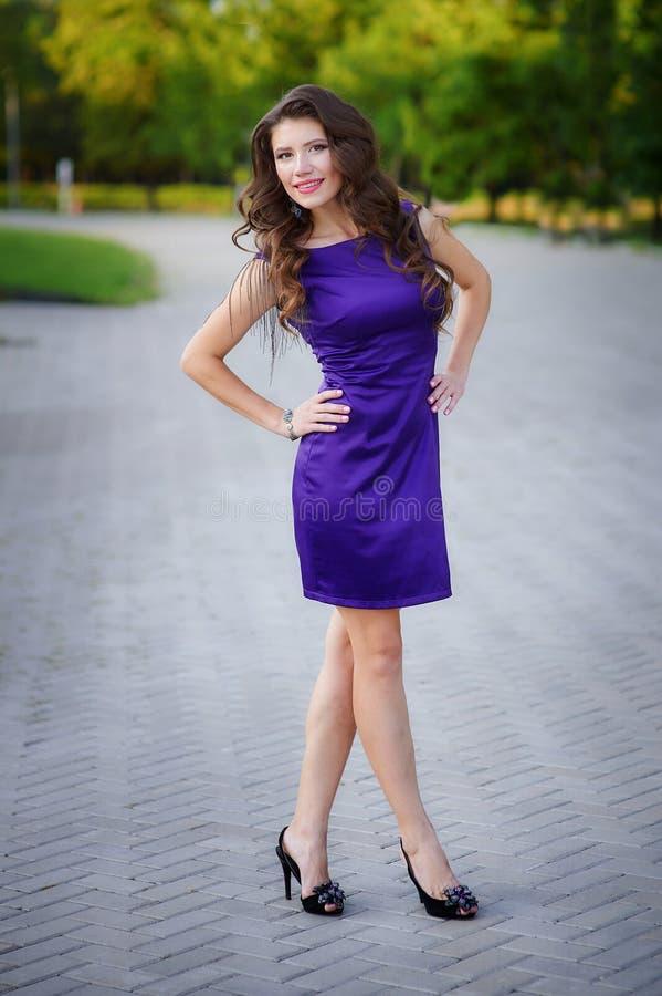 Mooie vrouw in purpere kleding in openlucht stock afbeeldingen