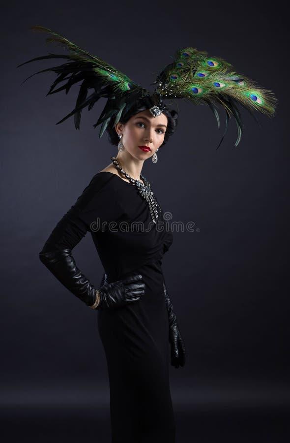 Mooie vrouw in retro stijl met veerdecoratie royalty-vrije stock fotografie