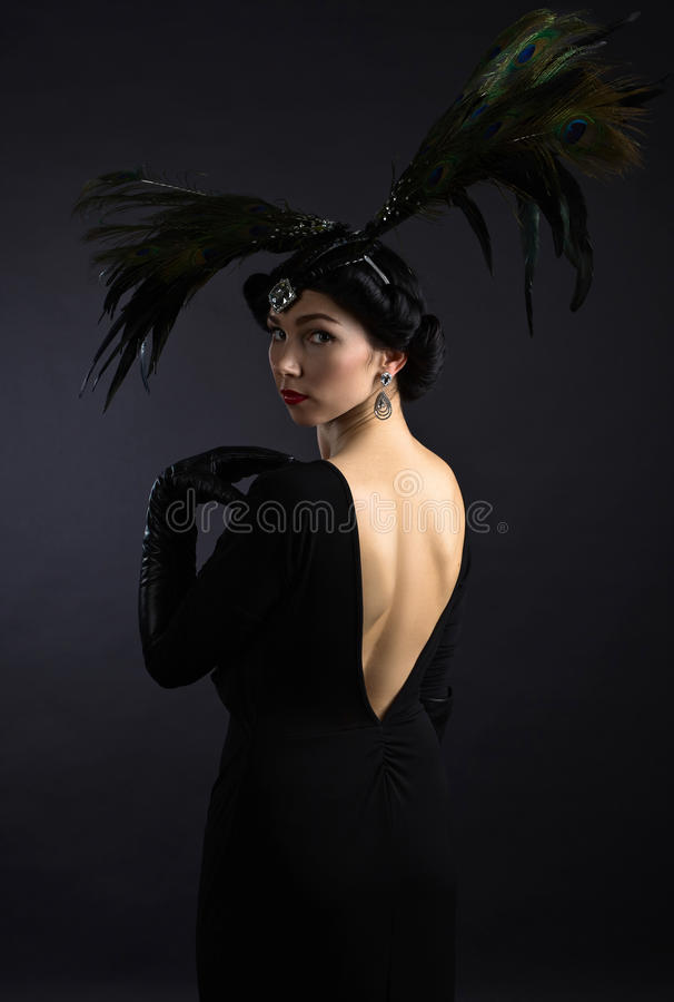 Mooie vrouw in retro stijl met veerdecration royalty-vrije stock fotografie