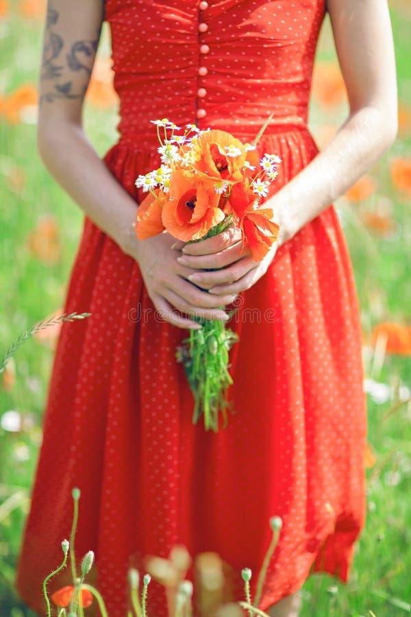 Mooie vrouw in rode kleding die zich in een holdingsbloemen van het papavergebied bevinden stock fotografie