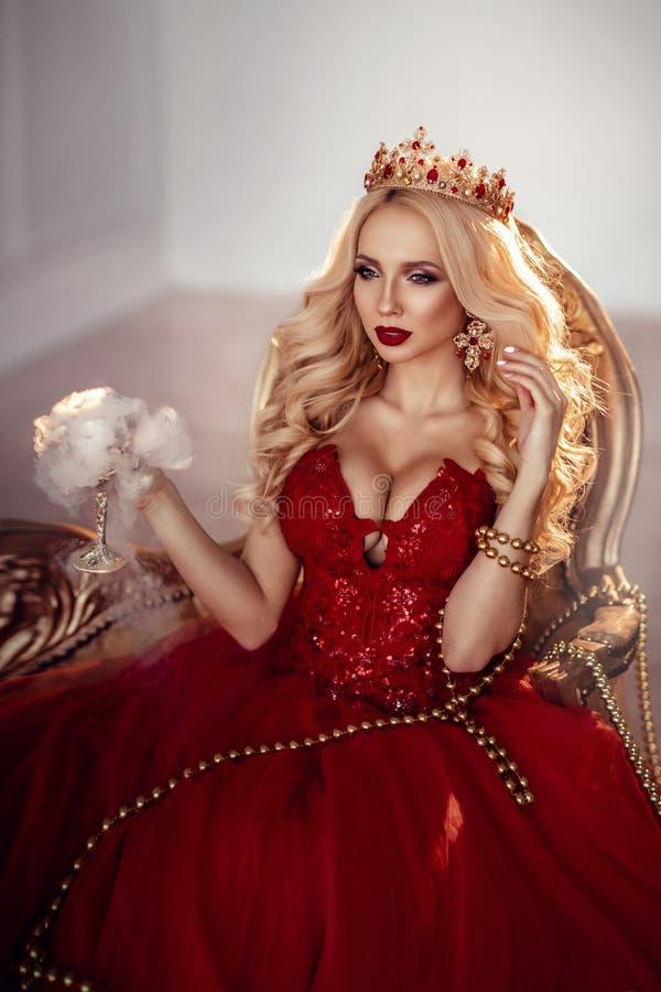 Mooie vrouw in rode kleding en kroon koningin Portret stock foto