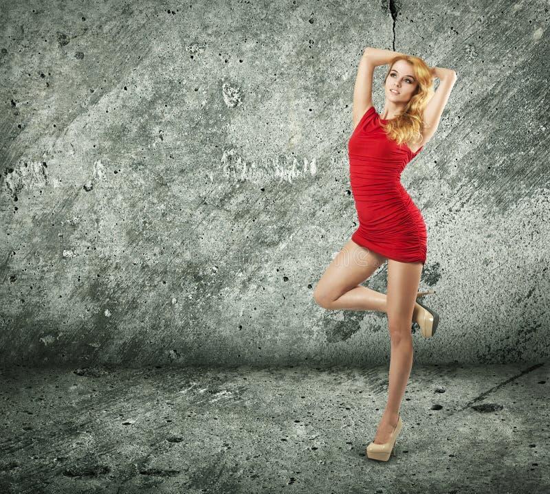 Mooie Vrouw in Rode Kleding op de Achtergrond van de Muur royalty-vrije stock afbeelding