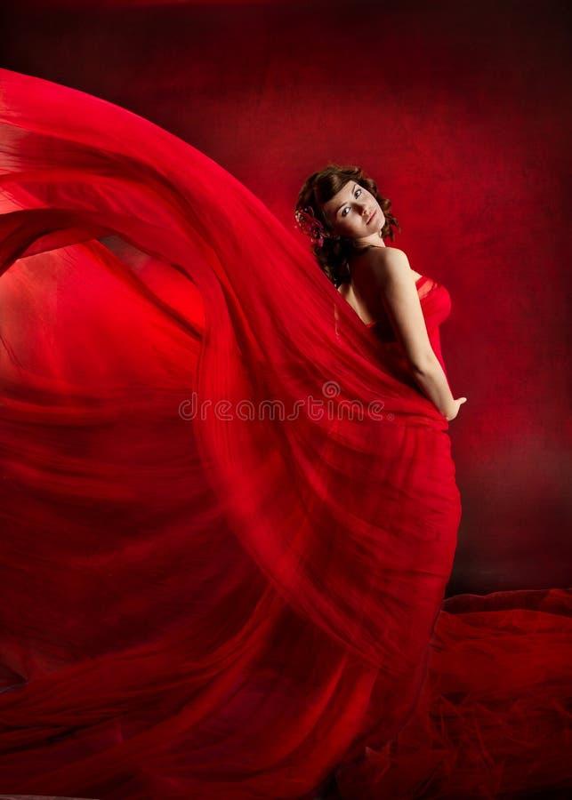 Mooie vrouw in rode vliegende golvende kleding. royalty-vrije stock foto's