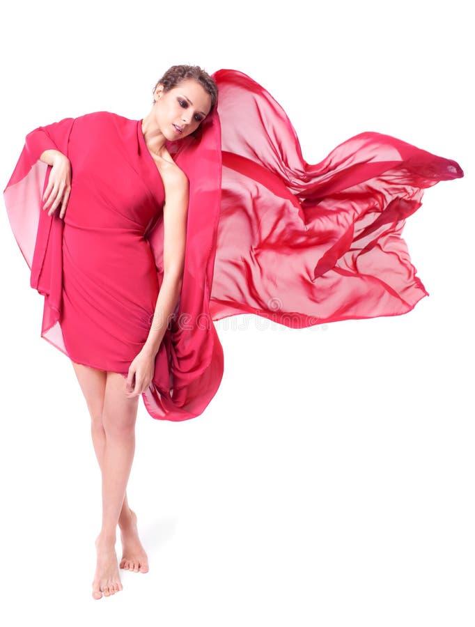 Mooie vrouw in rode vliegende kleding stock afbeeldingen